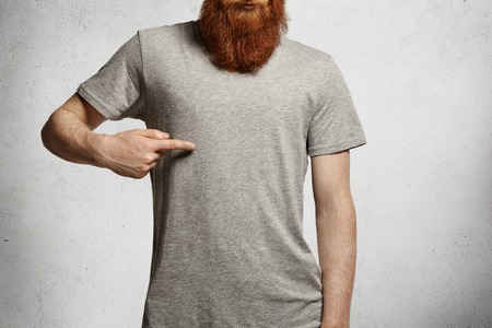 Design and advertising concept. Cropped shot of stylish young man with hipster red beard pointing index finger at copy space on his casual gray t-shirt, standing indoors against concrete wall