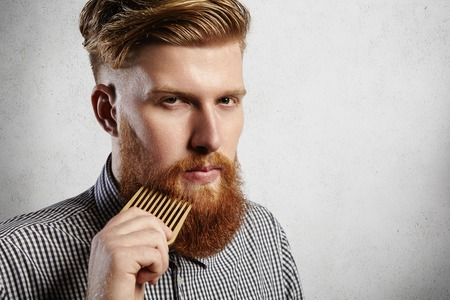 Portrait of young attractive redhead hipster male with serious and confident look, holding wooden comb and doing his thick beard. Stylish bearded barber in checkered shirt combing in salon. Horizontal Stockfoto