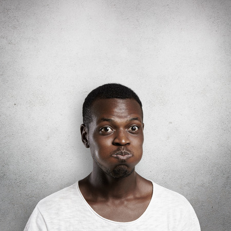 Body language concept. Young dark-skinned man puffing cheeks, trying hard to hold his breath, nearly bursting out laughing at something funny or ridiculous, showing his surprise and astonishment Stock Photo
