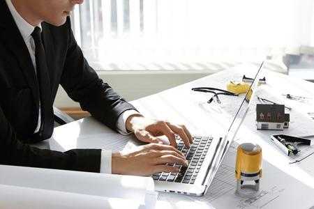 Gewöhnliche Arbeitstag von Unternehmen Baudirektor sitzen am Tisch mit Notebook, Arbeitszeichnungen und maßstabgetreues Modell Haus. Junge CEO auf Laptop eingeben, wartet auf seine Mitarbeiter in seinem Büro zu treffen
