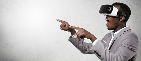 Headshot of excited dark-skinned businessman experiencing virtual reality, using 3d headset gesturing as if watching something astonishing, opening his mouth wide open and pointing with his fingers
