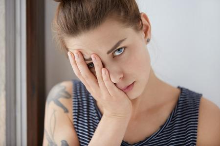 Mooi portret van verveelde vrouwelijke rust helft van haar gezicht op haar handpalm. Aantrekkelijk meisje met bruin haar en blauwe ogen moe van wonky gesprek, probeert te verbergen van saai gesprek onder haar arm.