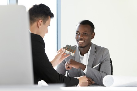 housing project: Two executives of construction company discussing new housing project. Caucasian chief engineer holding scale model house presenting prototype to his African boss, looking happy with executed work Stock Photo