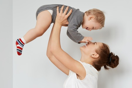 sincerely: Nice shot of happy mother and child on the white background. Young attractive woman with bunch of brown hair rising blond son, sincerely smiling. Pleased baby touching her face in endless joy.