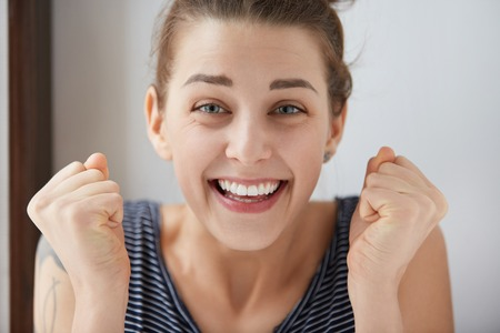 Happy young Caucasian woman bursting with joy and pleasure. Beautiful girl with blue eyes doubles her fists in winning mindset, smiling with open-wide mouth, showing her perfect white teeth. Stock Photo