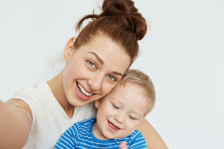 toothless: Positive family selfie with young mommy and toothless kid smiling together on white background. Playful state of mind and happy mood of attractive woman makes this shot fabulous, heartwarming.