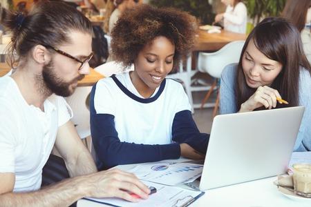 jovenes empresarios: El trabajo en equipo y el concepto de la cooperación. Tres jóvenes empresarios discutiendo asuntos de negocios usando el ordenador portátil, el emplazamiento en la cafetería, hacer el papeleo, el intercambio de ideas y planes, buscando entusiasta
