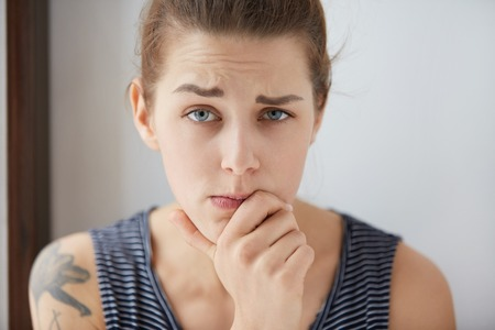 desconfianza: Suspicious Caucasian female frowning eyebrows in disbelief. Attractive young girl resting her chin on hand, covering mouth in distrust to the words of her interlocutor. You wont fool her anyway. Foto de archivo
