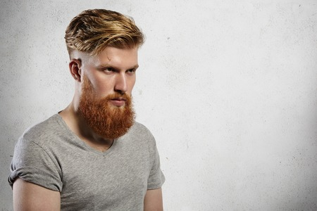 sullenly: Portrait of courageous and fashionable male model with long trendy beard and undercut hairstyle. Caucasian blond man in grey T-shirt looking sullenly ahead of him. Indoors shot on white background.
