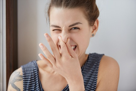 unpleasant: Close-up shot of Caucasian girl showing disgust, pinching her nose to avoid bad smell. Brunette girl with bunch of hair narrowing eyes in aversion to awful stink. Negative emotions, nasty feelings.