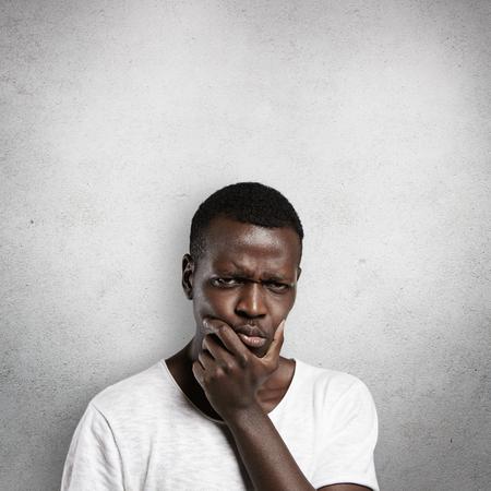 dudando: Headshot de grave desconcertado joven africano que toca su barbilla, mirando reflexivo y escépticos acerca de algo, profundamente en pensamientos, dudando en tomar la decisión, con el ceño fruncido. emociones y sensaciones humanas