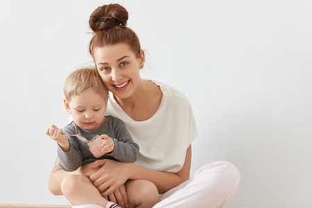 Beautiful portrait of young mother and child sitting together on white background. Happy Caucasian female with bunch of brown hair in white clothes holding baby in her arms, sincerely smiling.