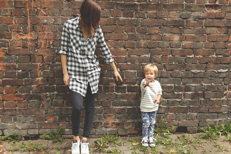 he   my sister: Shot of little boy with his caring sister near brick wall. Skinny Caucasian girl dressed in checked shirt, black trousers. She stretching arm to younger brother, but he pulling his hand ahead. Stock Photo
