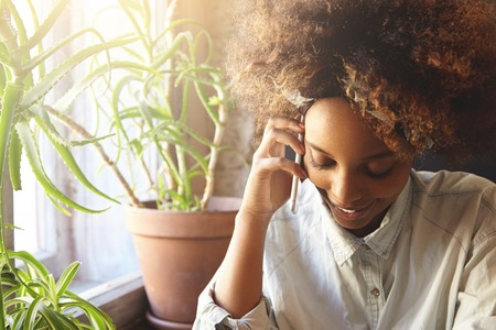 People and lifestyle concept. Attractive fashionable dark-skinned student girl with Afro hairstyle, dressed in stylish clothes, talking on mobile phone, inviting friends to join her at cafe for coffee