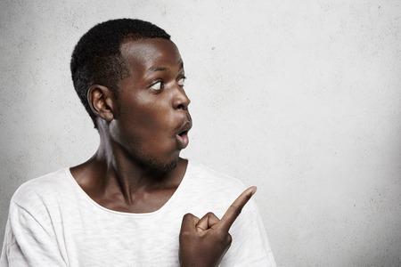 広告の概念。大売り出し、広く彼の口を開くと空白のコピー スペースの壁に彼の人差し指を指している浅黒い肌のお客様が気軽に、服を着てヤング