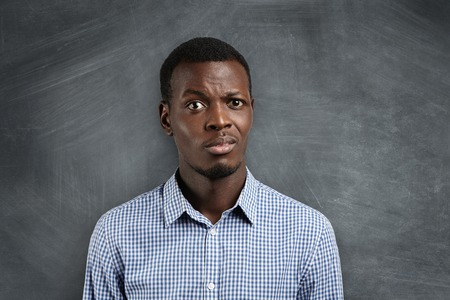 displeased: Shocked dark-skinned teacher surprised with his pupils misbehavior during his first day at school. Astonished student in shirt standing at blackboard, not ready with homework, looking displeased Stock Photo