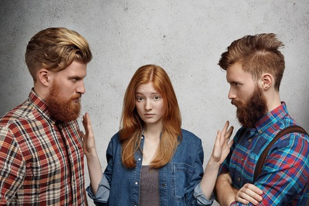 adultery: Love triangle, adultery, relationships and hard choice problem. Young beautiful woman looking confused and unsure while choosing between two guys. Angry rivals standing face to face, fighting for girl Stock Photo