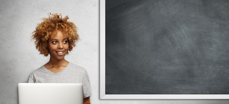 Attractive African student with Afro hairstyle and cute smile, looking aside with pensive expression, using free Internet connection on laptop computer, doing classwork, sitting at blackboard