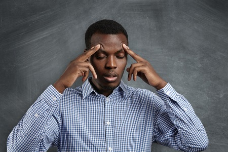 robbing: Handsome serious puzzled African student dressed in checkered shirt robbing his forehead, closing his eyes, looking concentrated and focused, trying to remember right answer during test in classroom