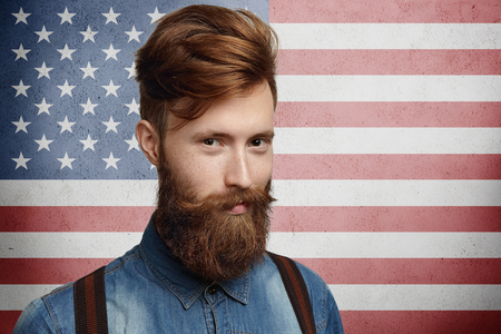 national identity: National identity and citizenship concept. Studio shot of good-looking unshaven Caucasian macho dressed in trendy clothes, looking at camera with attractive smile posing on American flag background