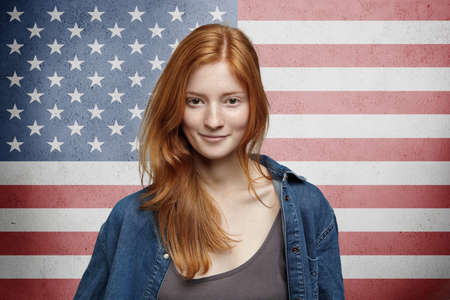 citizenship: US citizenship and patriotism concept. Portrait of pretty American girl with long red hair wearing denim jacket, looking with cute smile with USA flag on background. Horizontal, studio shot, isolated Stock Photo