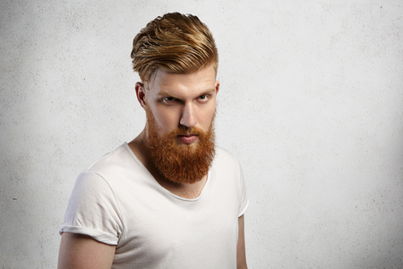 muscular build: Headshot of self-assured bearded hipster with stylish haircut and muscular build wearing t-shirt with rolled sleeves looking with severe expression, angry with something. Isolated shot, horizontal