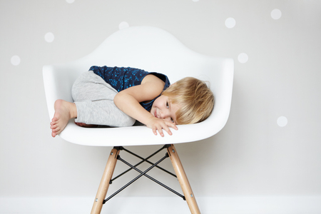 designer baby: Happy carefree childhood. Sweet Caucasian infant rolling himself up in white designer chair, hiding from his friends while playing hide-and-seek. Cute baby boy having fun indoors. Visual effects