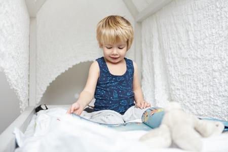 interested baby: Portrait of beautiful Caucasian baby boy with fair hair dressed in pajamas sitting on white canopy bed, absorbed in reading childrens book, looking through pictures with interested expression Stock Photo