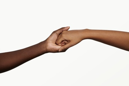 trust people: Two African people holding their hands tight together. Friendship, love, trust and support concept between man and woman: male and female touching each other in tender handshake showing togetherness