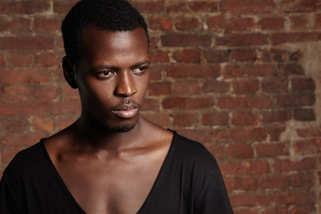 redbrick: Indoor shot of young African male model with athletic body wearing black stylish T-shirt with scooped neck standing against red-brick wall with copy space for your text or promotional content