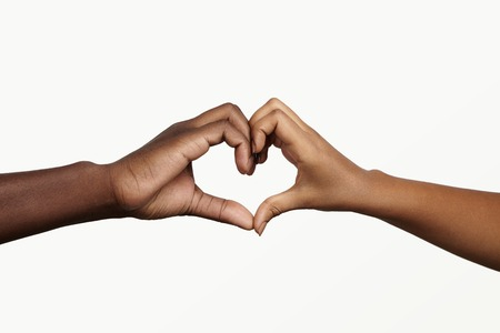 Two young dark-skinned people holding hands in shape of heart, symbolizing love, peace and unity. African man and woman showing heart-shaped hand gesture, expressing affection and togetherness Stock Photo