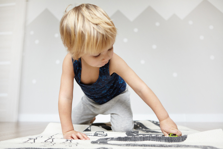 Indoor shot of adorable Caucasian two-year old baby boy with fair hair holding toy car while playing on carpet indoors in childrens room or nursery, looking with interest. Sweet toddler having fun