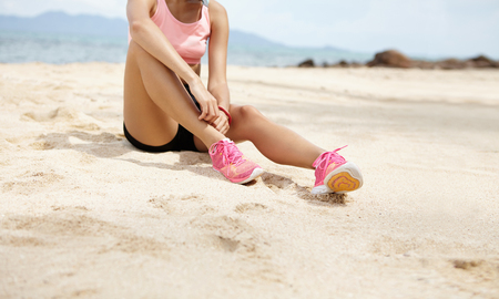 exersice: Young woman jogger with beautiful fit legs sitting on sandy beach and relaxing during break after hard workout. Female runner enjoying rest after active physical exersice outdoors. Cropped view Stock Photo