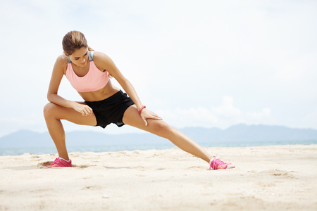 cardio workout: Young female runner with beautiful fit body warming-up her muscles before strength training cardio workout. Woman athlete in sportswear stretching legs with lunge hamstring stretch exercise on beach