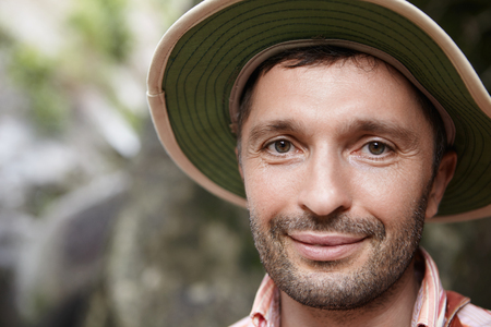 Close up of handsome ecologist with stubble and joyful smile posing outdoors at rocks while working in nature park, conducting scientific study. Happy smiling biologist in panama hat at field work Stock Photo