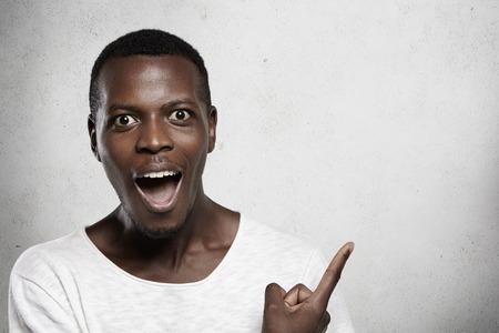 屋内白を身に着けているアフリカの男性の肖像画 t シャツを持つ驚かれ、驚く見て、口を広く開いて、人差し指で空白のスタジオの壁に示します。