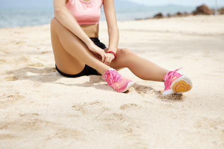 Female runner with beautiful legs wearing pink running shoes sitting on sandy beach, having small break after active running workout outdoors at the ocean. Cropped view, shallow depth of field