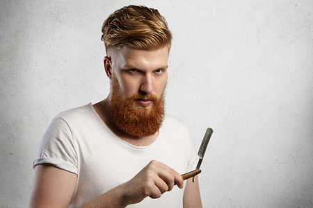 his shirt sleeves: Handsome barber with thick beard holding his barbershop accessory, demonstrating sharp blade of straight razor. Stylish hairdresser in white t-shirt with rolled up sleeves ready to shave his clients