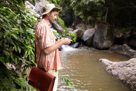 Side view of male biologist with leather bag at field work conducting water analysis standing at mountain river and taking pictures using digital tablet with waterfall and rocks on background