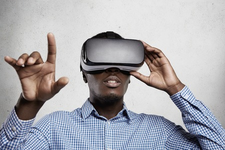 3d technology, virtual reality and entertainment concept. African businessman playing simulation games with oculus rift support wearing headset with head-mounted display and gesturing with his finger