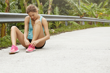 cross ties: Young tired Caucasian woman runner lacing her pink running shoes, sitting on road in tropical forest having small break while jogging outdoors. Female jogger tying laces on her sneakers during workout