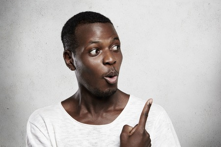 astonishing: African male model in white t-shirt looking with shocked expression at blank wall, pointing finger at copy space for your advertising content. Dark-skinned man surprised with astonishing advertisement