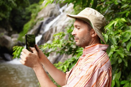 Nature, ecology and science concept. Serious biologist in striped shirt holding touch pad, taking picture or recording video of beautiful wildlife in rainforest while studying its bio-diversity Stock Photo