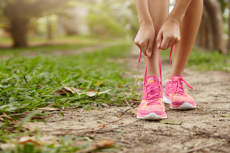 Caucasian athletic woman tying laces on her pink running shoes before jogging standing on footpath in forest. Female runner lacing her sneakers while doing workout in rural area. Film effect