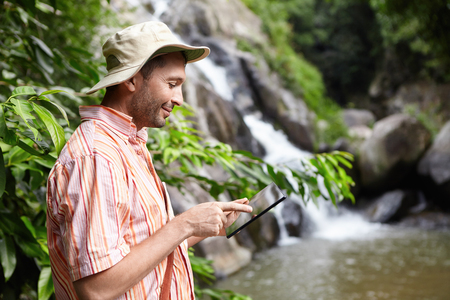 Bearded botanist wearing panama hat using digital tablet pointing at blank screen with happy expression, standing at mountain river against waterfall background while conducting water analysis Stock Photo