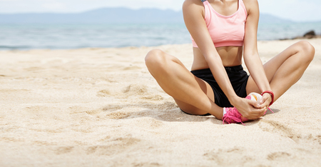 Woman runner doing butterfly stretch, placing hands on top of her feet during warm-up routine on beach before run, preparing legs for cardio workout, sitting on beach against blurred sea background