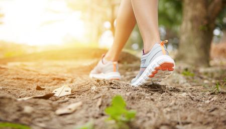 森の道で中にスニーカーで女性ランナーを実行します。屋外、深刻なマラソンの準備運動をしながら実行している女性のジョガーの背面図をトリミ