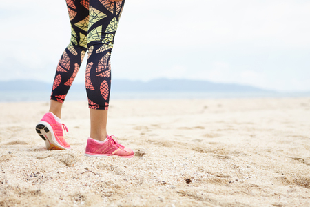 footprints in sand: Sports and healthy lifestyle concept. Cropped shot of legs of girl athlete against ocean beach. Female runner in colorful leggings and pink running shoes standing on sand during workout in open air Stock Photo