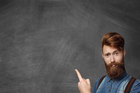 Hipster bearded man has idea, pointing his finger up, looking with amused expression, standing isolated in bottom right-hand corner of blank chalkboard with copy space for your promotional content