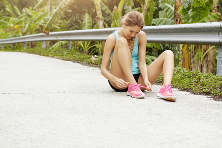 Sports and healthy lifestyle concept. Young sporty girl sitting on road lacing her pink sneakers during jogging exercise outdoors. Blonde woman athlete in sportswear taking rest and tying shoelaces